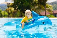 Kind im Swimmingpool Kind auf aufblasbarem Floss lizenzfreie stockbilder