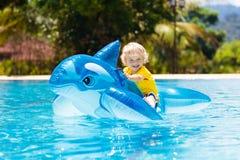 Kind im Swimmingpool Kind auf aufblasbarem Floss stockbilder