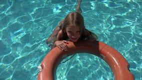 Kind im Swimmingpool, glückliches kleines Mädchen, das im Wasser, Sommer-Ferien 4K sich entspannt stock video footage