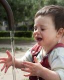 Kind im Wasserbrunnen Stockbild
