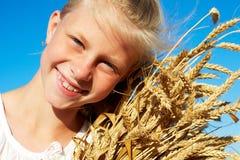 Kind im weißen Hemd, das Weizenähren in den Händen hält Stockbild
