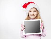 Kind im Weihnachtshut mit Tablette Stockbilder