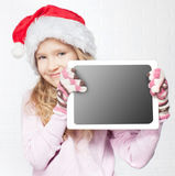 Kind im Weihnachtshut mit Tablette Lizenzfreies Stockbild