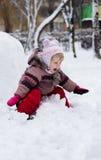 Kind im Winter Mädchen, das unten die Hügel rollt lizenzfreies stockfoto