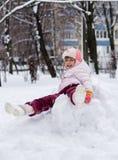 Kind im Winter Mädchen, das unten die Hügel rollt lizenzfreie stockfotos