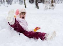 Kind im Winter Mädchen, das unten die Hügel rollt lizenzfreies stockbild
