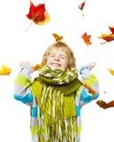 Kind im woolen Schal, der mit Ahornblättern spielt Lizenzfreie Stockfotos