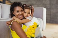 Kind international mommy embracing her little daughter. Express positivity. Beautiful dark-skinned female feeling happiness while holding colorful bouquet stock images