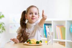 Kind isst das gesunde Lebensmittel, das sich Daumen zeigt Stockfoto