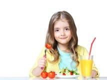 Kind isst den Gemüsegetränksaft, der auf Weiß lokalisiert wird stockfoto