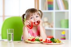 Kind isst gesundes Lebensmittel im Kindergarten oder zu Hause lizenzfreie stockfotografie