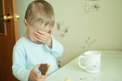 Kind isst mit Rissen Stockfotografie