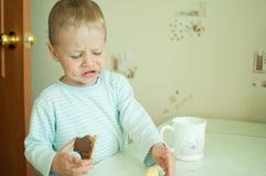 Kind isst mit Rissen Stockfoto