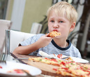 Kind isst Pizza. Stockfotos
