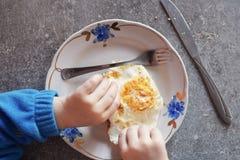 Kind isst Spiegelei mit den Händen, Messer und Gabel Lizenzfreie Stockfotografie