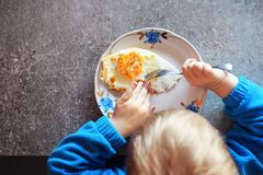 Kind isst Spiegelei mit Gabel Lizenzfreie Stockfotografie