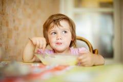 Kind isst von der Platte mit Löffel Stockfotografie