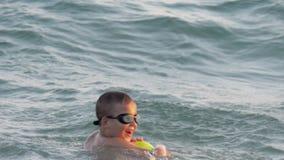 Kind ist glücklich, auf Meereswellen zu schwimmen stock video