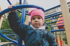 Kind 4-5 jaar die op schroefpijp bij de hoogte van de Speelplaats zitten Royalty-vrije Stock Fotografie