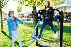 Kind in jeansoefening die een gymnastiekmachine in werking stellen openlucht royalty-vrije stock foto's