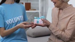 Kind lady volunteer giving gift box for happy elderly woman, little surprise stock footage