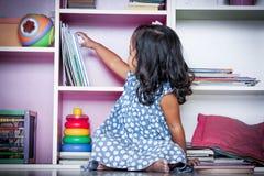 Kind las, das nette kleine Mädchen, das ein Buch auf Bücherregal vorwählt Lizenzfreie Stockfotografie