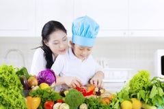 Kind lernt, Gemüse in der Küche zu schneiden lizenzfreie stockbilder