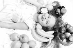 Kind, leuk babymeisje die met kleurrijke vruchten in mand leggen stock afbeeldingen