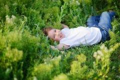 Kind liegt auf dem Gras Lizenzfreie Stockfotografie