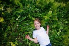Kind liegt auf dem Gras Stockfoto