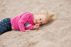 Kind liegt auf dem Strand Stockbild