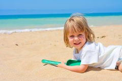 Kind liegt auf Pebble Beach, Lizenzfreie Stockfotos