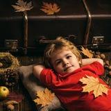 Kind liegt, Hände hinter Kopf legend und auf Bretterboden in den goldenen Blättern stillstehend Größte Rabatte für alle Herbstkle lizenzfreie stockfotografie