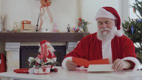 Santa Claus read wish letters from children. Kind looking Santa Claus in red costume near bright decorated fir tree and fireplace reads Christmas letters. Old stock video footage