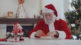 Santa reads Christmas letters. Kind looking Santa Claus in red costume near bright decorated fir tree and fireplace reads Christmas letters. Old man is happy and stock video