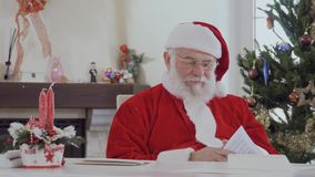 Santa Claus read letters from children. Kind looking Santa Claus in red costume near bright decorated fir tree and fireplace reads Christmas letters. Old man is stock video footage