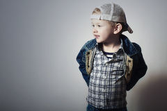 Kind. Lustiges Little Boy in den Jeans. Fernlastfahrerkappe. Freude. Modernes Kind. kariertes Hemd. Denim-Abnutzung Stockbild
