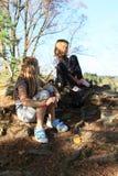 Kind - Mädchen, das auf Socken und Schuhe sich setzt Stockbilder