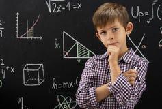 Kind macht Berechnungen auf der Tafel stockfoto