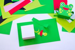 Kind macht einen Frosch aus Papier heraus lizenzfreies stockbild