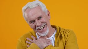 Kind male pensioner admiring on orange background, looking with love, good news stock video