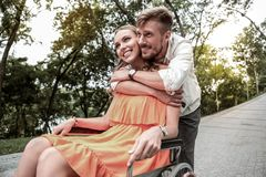 Kind male person embracing his pretty girlfriend. Best friend. Cheerful young people expressing positivity while looking in one direction stock images