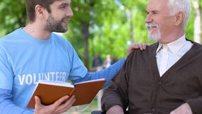 Kind male volunteer reading book to smiling old man in wheelchair, assistance. Stock footage stock footage