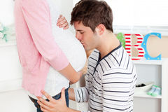 Kind man kissing his pregnant wife's belly Royalty Free Stock Photo