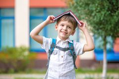 Kind met boek op zijn hoofd in openlucht stock afbeelding