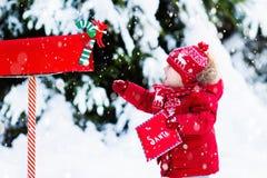 Kind met brief aan Kerstman bij Kerstmisbrievenbus in sneeuw Royalty-vrije Stock Afbeeldingen