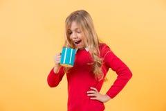 Kind met de verraste blauwe kop van de gezichtsgreep op oranje achtergrond Royalty-vrije Stock Afbeelding