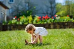 Kind met een konijn op het gras stock foto's
