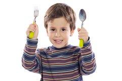 Kind met een lepel en een vork royalty-vrije stock fotografie