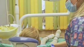 Kind met een moeder bij een tandarts` s ontvangst Het meisje ligt als voorzitter, achter haar moeder De artsenwerken met stock footage